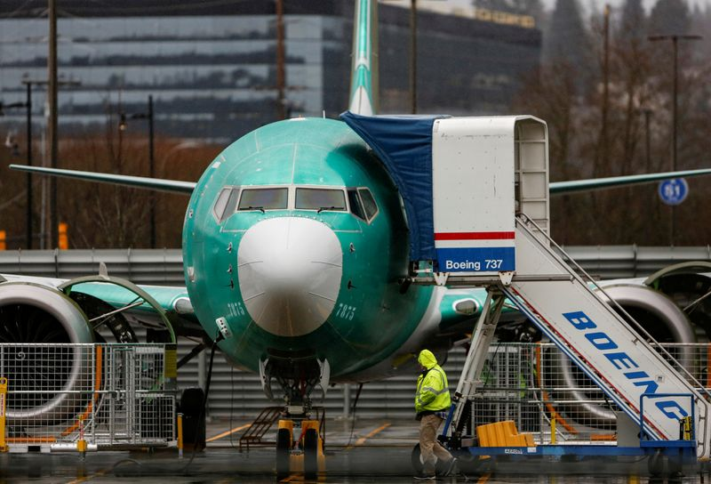 An employee walks past a Boeing 737 Max aircraft seen parked at the Renton Municipal Airport in Renton