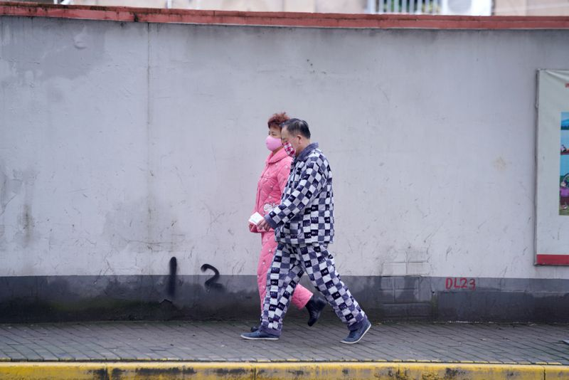 Residents wearing face masks and pyjamas are seen on a street in Shanghai