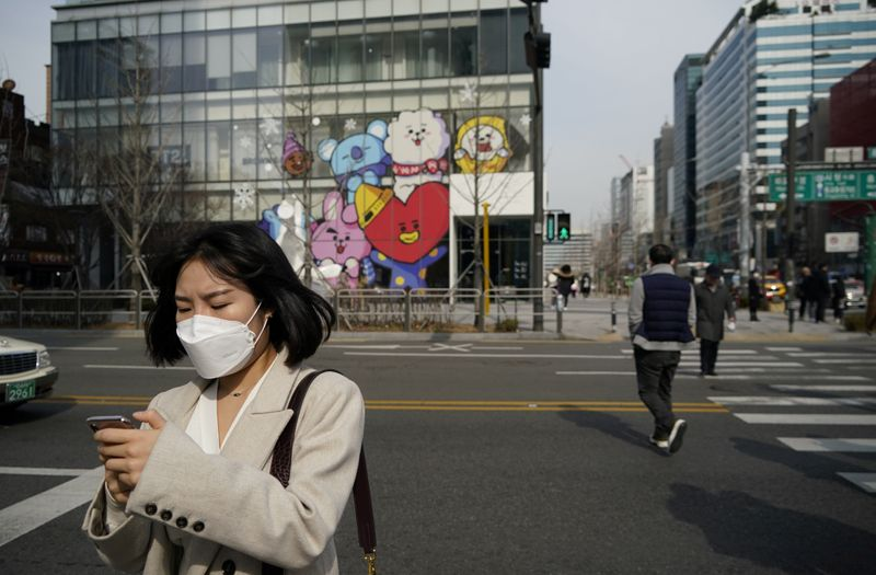 A woman wearing a mask to prevent the coronavirus uses her mobile phone at a shopping district in Seoul
