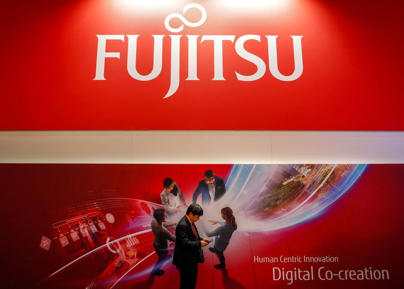 A man looks at his mobile in front of a Fujitsu advert during the Mobile World Congress in Barcelona