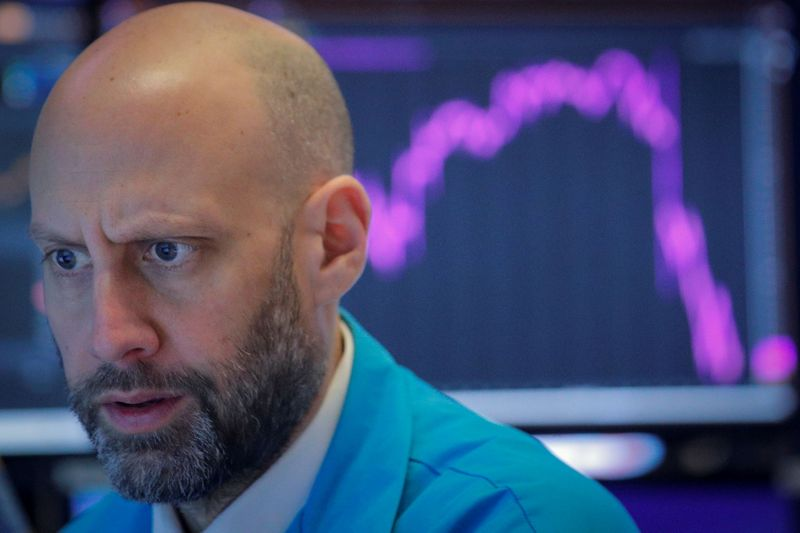FILE PHOTO: A trader work on the floor at the NYSE in New York on Feb 27, 2020