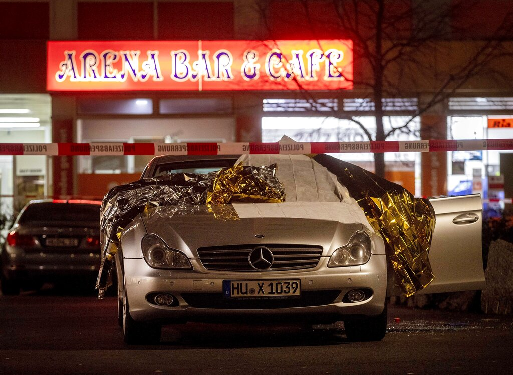 A car covered with rescue blankets stands in front of a bar in Hanau Germany Thursday Feb. 20 2020