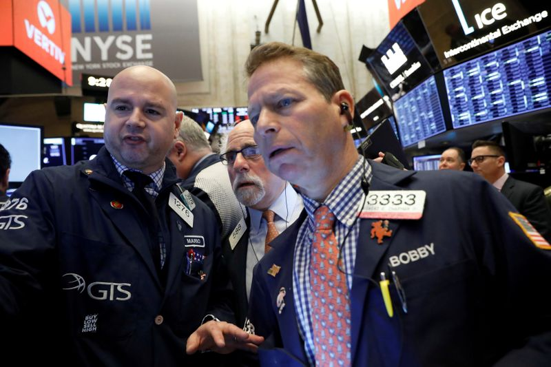 FILE PHOTO: Traders work on the floor at the NYSE in New York