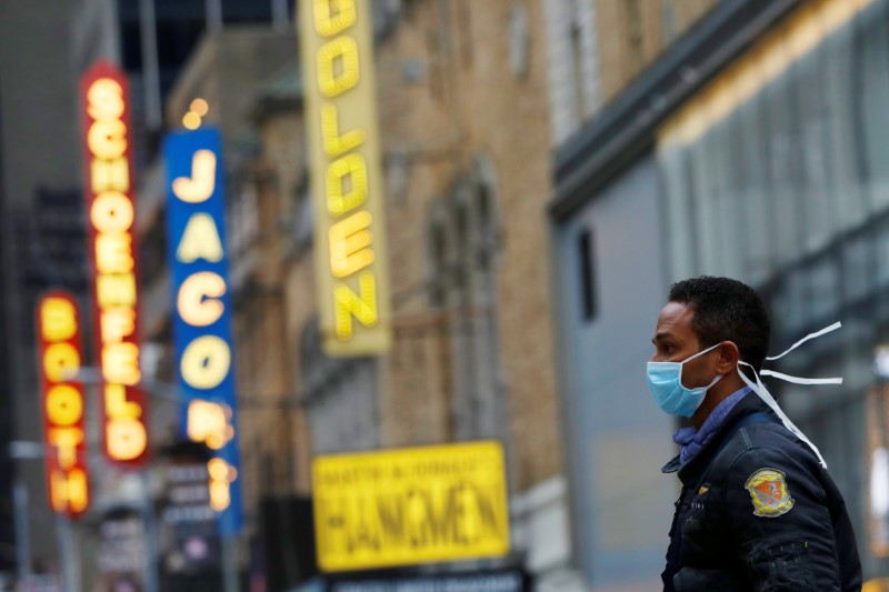 A man in a surgical mask walks through Manhattan's Broadway Theatre district after Broadway shows announced they will cancel performances due to the coronavirus outbreak in Manhattan, New York City