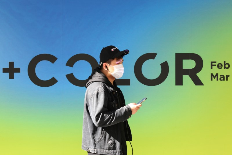FILE PHOTO: Man, wearing a protective mask, checks his mobile phone in central Madrid