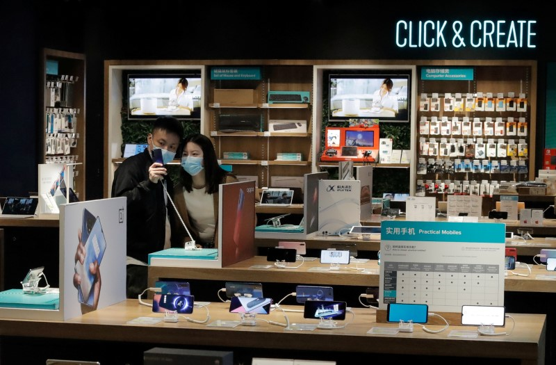 FILE PHOTO: People wearing protective masks look at phones at an electronic retailer in Beijing