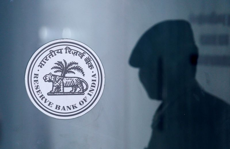 A security guard's reflection is seen next to the logo of the Reserve Bank Of India (RBI) at the RBI headquarters in Mumbai
