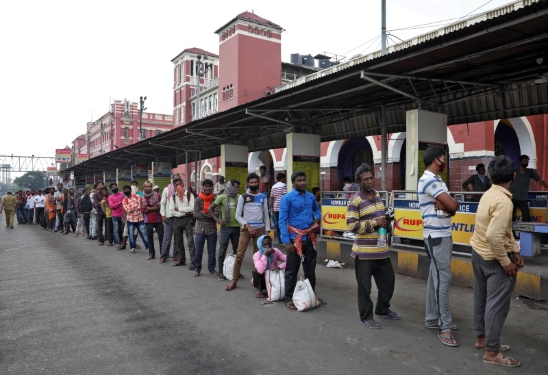 Migrant workers wait in a queue to receive free food outside Howrah railway station after India ordered a 21-day nationwide lockdown to limit the spreading of Coronavirus disease (COVID-19), in Kolkata