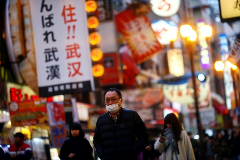FILE PHOTO: A man, wearing protective mask following an outbreak of the coronavirus disease (COVID-19), walks on an almost empty street in the Dotonbori entertainment district of Osaka