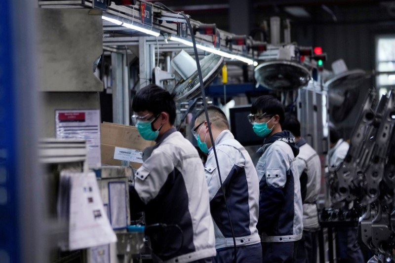 Employees wearing face masks work on a car seat assembly line at Yanfeng Adient factory in Shanghai