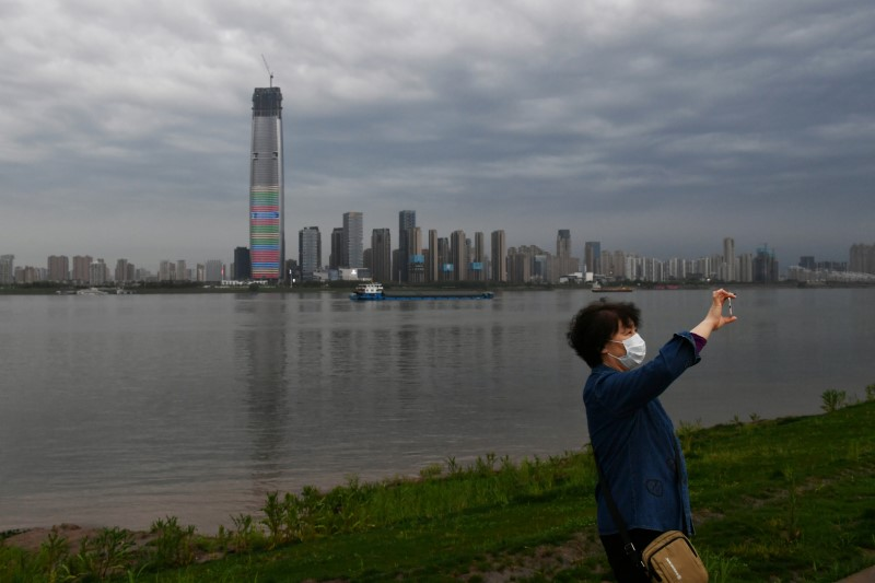 Woman wearing a face mask takes pictures with a mobile phone at a riverside park in Wuhan