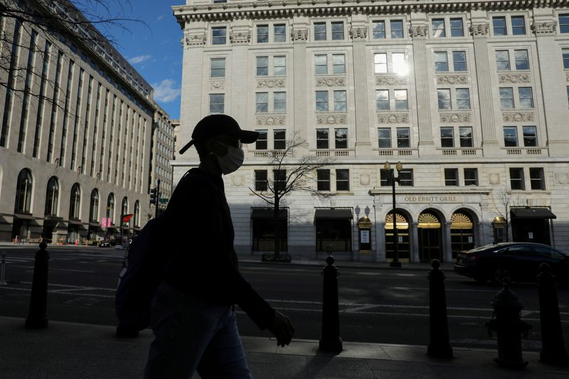 FILE PHOTO: A person in a mask walks on a nearly empty street in the coronavirus outbreak near the Treasury Department in Washington