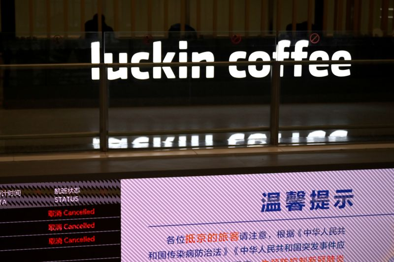 FILE PHOTO: Sign of Luckin Coffee is seen behind an information board showing cancelled flights, at the Beijing Daxing International Airport, as the country is hit by an outbreak of the novel coronavirus, in Beijing