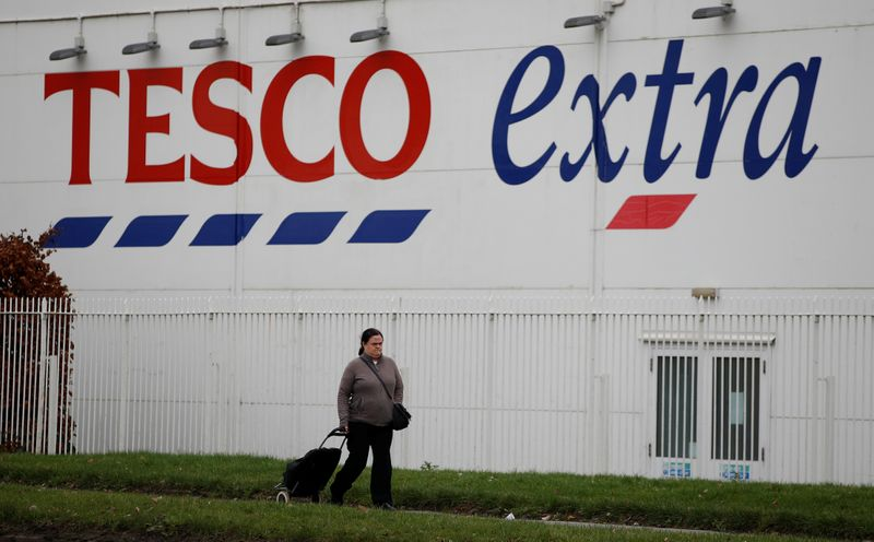 FILE PHOTO:  A woman walks past a Tesco extra superstore near Manchester