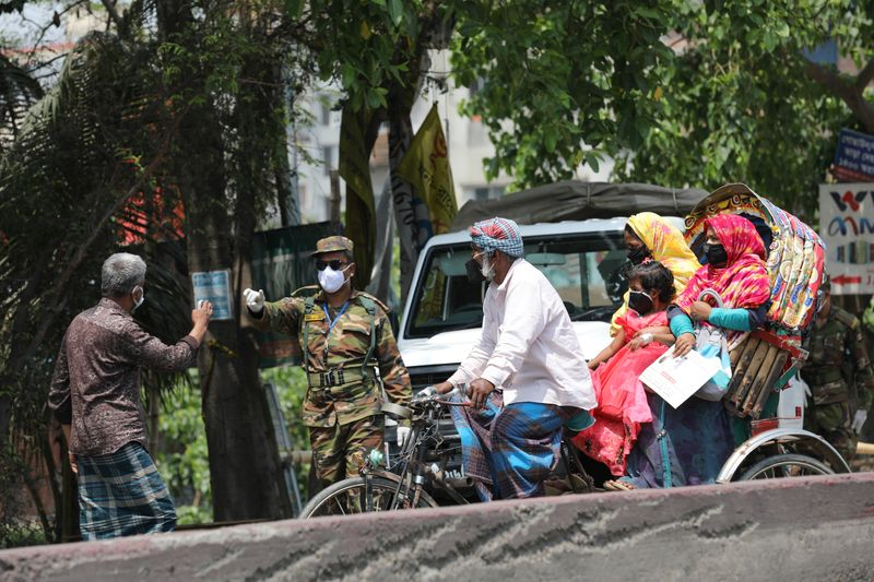 An army personnel stops people riding on a rickshaw at a check post during government imposed countrywide shutdown amid concerns over the coronavirus disease (COVID-19) outbreak in Narayanganj
