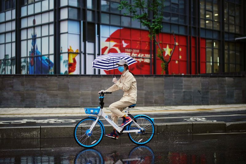 Woman rides a shared bicycle past an image of the Chinese flag in Wuhan