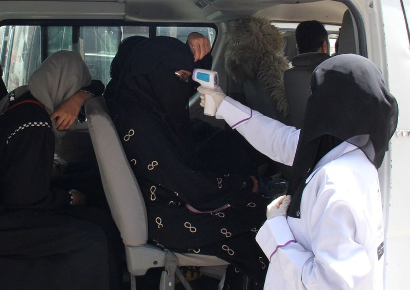 A health worker takes temperature of passengers of a van, amid fear of coronavirus disease (COVID-19), on the outskirts of Taiz