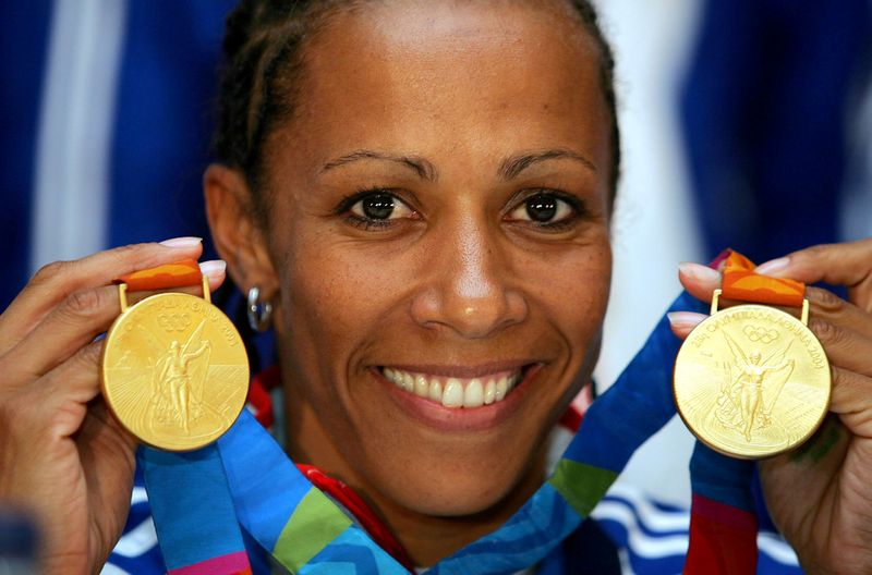 FILE PHOTO: Kelly Holmes, Olympic champion over 800m and 1500m, displays her two gold medals minutes after her a..