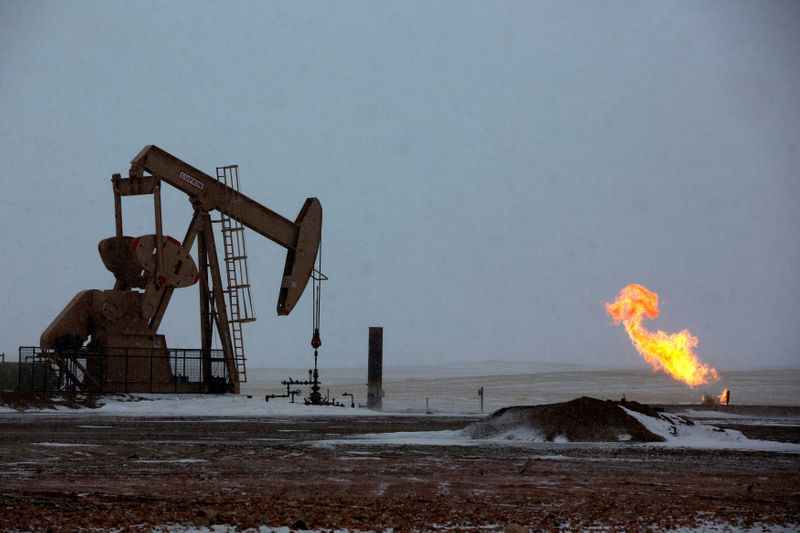 FILE PHOTO: Natural gas flares are seen at an oil pump site outside of Williston