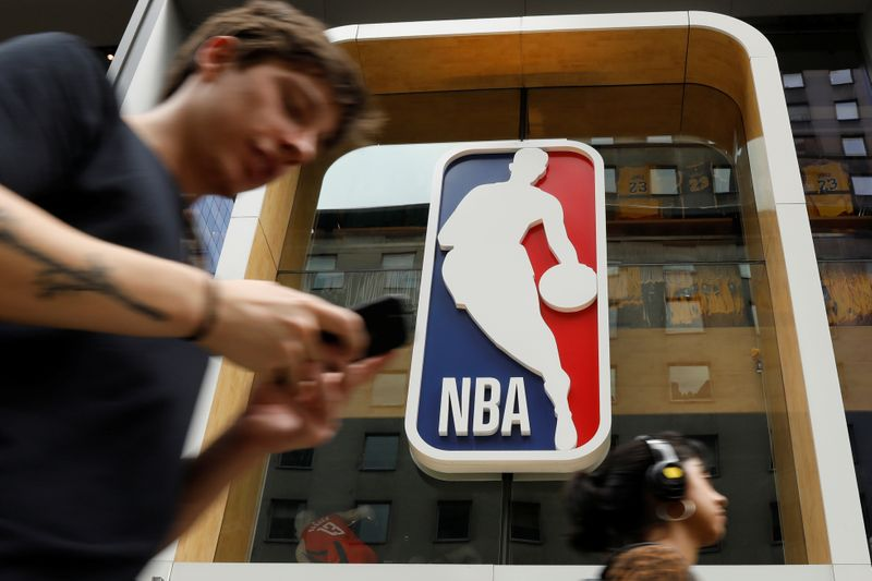 FILE PHOTO:  The NBA logo is displayed as people pass by the NBA Store in New York