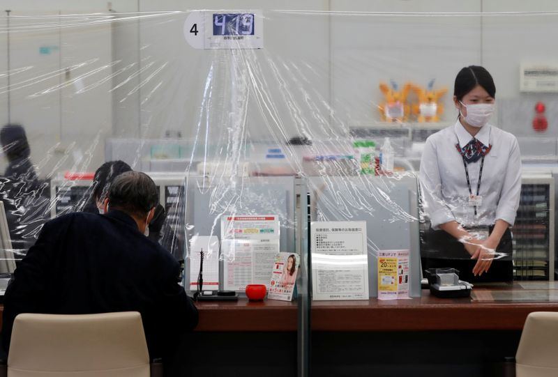 A bank teller wearing a protective face mask stands at a counter where a plastic curtain is installed in order to prevent infections following the coronavirus disease (COVID-19) outbreak, at the Higashinakano branch of MUFG Bank in Tokyo