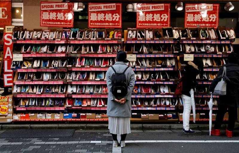 FILE PHOTO: A woman looks at shoes on sale at an outlet store in Tokyo's shopping district