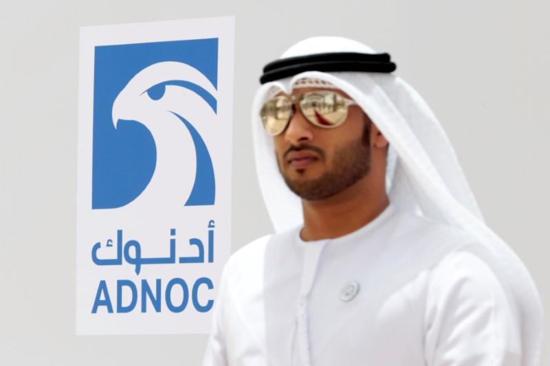 An Emirati man is seen near the logo of  ADNOC in Ruwais