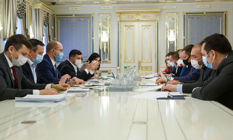 Ukrainian President Volodymyr Zelenskiy, government officials and businessmen, attend a meeting wearing a protective masks in Kiev,