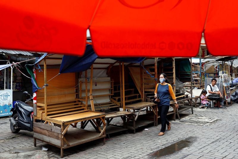 A woman wearing a protective face mask walks past closed street vendors booths at a traditional market amid the spread of the coronavirus disease (COVID-19) in Jakarta