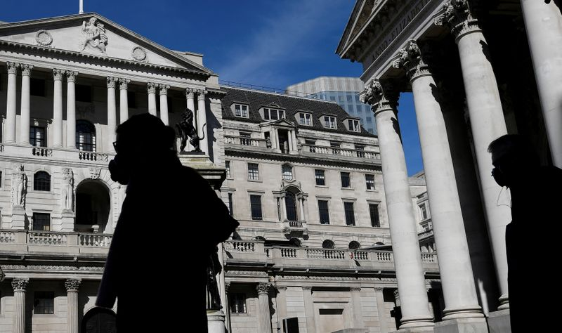 FILE PHOTO: People wearing masks walk past the Bank of England