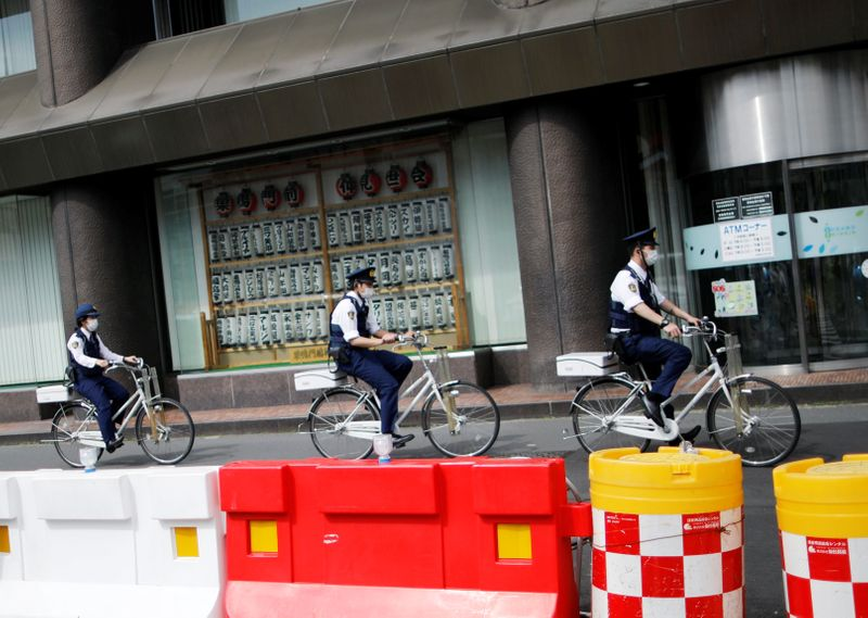 FILE PHOTO:  Police officers wearing protective face masks ride bicycles on the street under a nationwide state of emergency as the spread of the coronavirus disease (COVID-19) continues in Tokyo