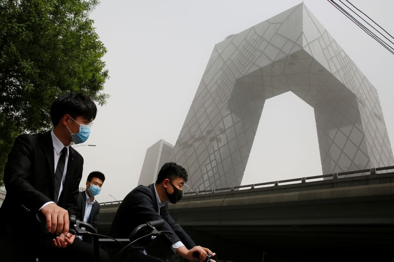 People wear face masks as they wait to cross a street near the CCTV headquarters during a dust storm in Beijing