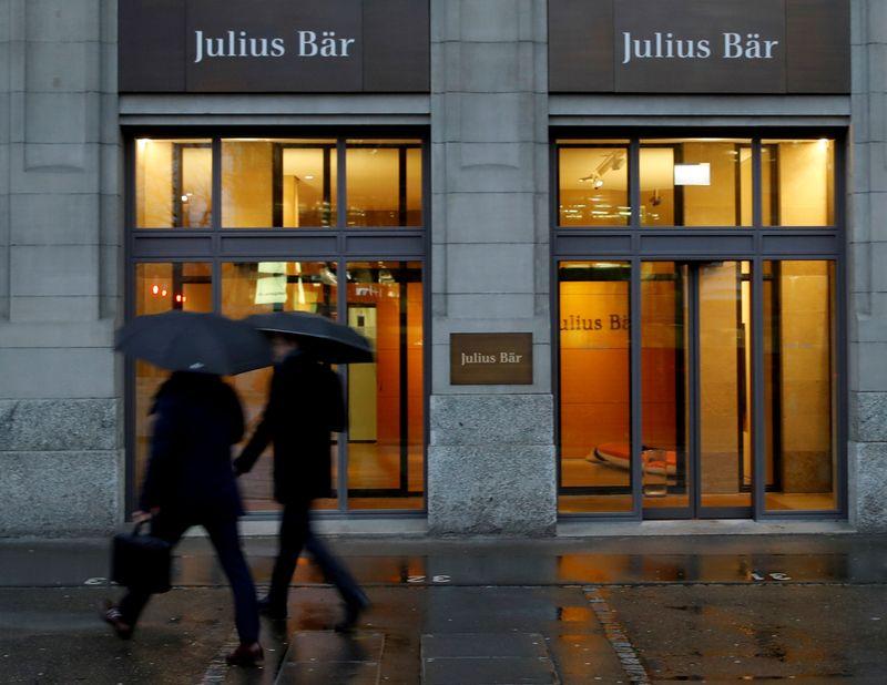 FILE PHOTO: People walk past a branch of Swiss bank Julius Baer in Zurich
