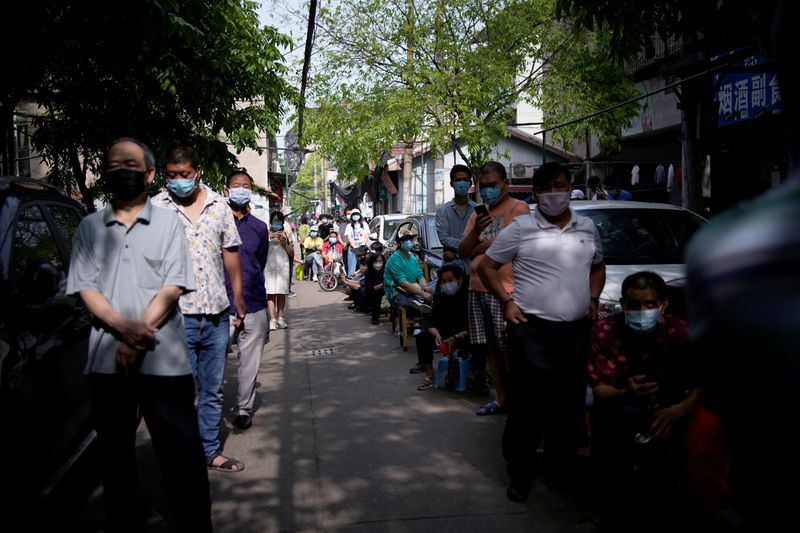 Residents wearing face masks line up for nucleic acid testings at a residential compound in Wuhan