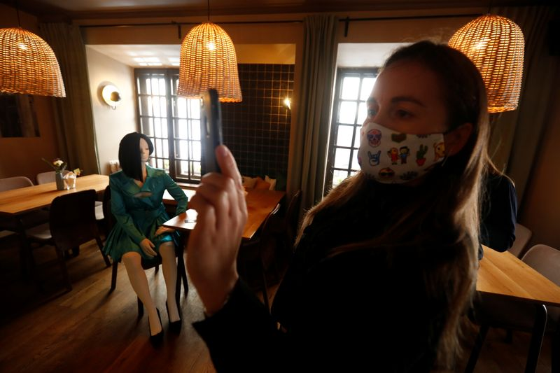 A woman wearing a protective face mask takes a picture of a mannequin inside a restaurant where mannequins dressed in creations of local designer sit at the table and bar, during the coronavirus disease (COVID-19) outbreak in Vilnius