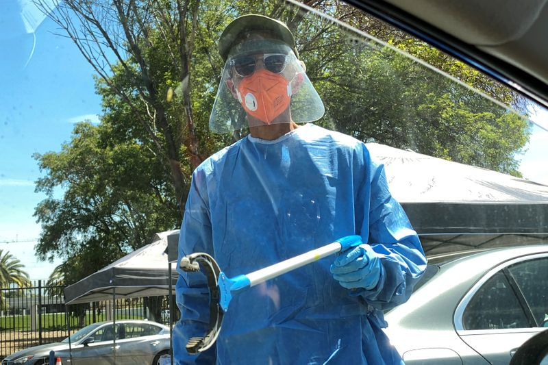FILE PHOTO: A healthcare worker reaches toward a car to grab a completed coronavirus diagnostic test, as the global outbreak of the coronavirus disease (COVID-19) continues, in Los Angeles
