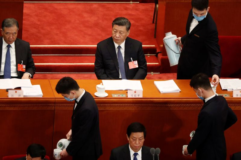 Attendants serve tea around Chinese President Xi Jinping at the opening session of NPC in Beijing