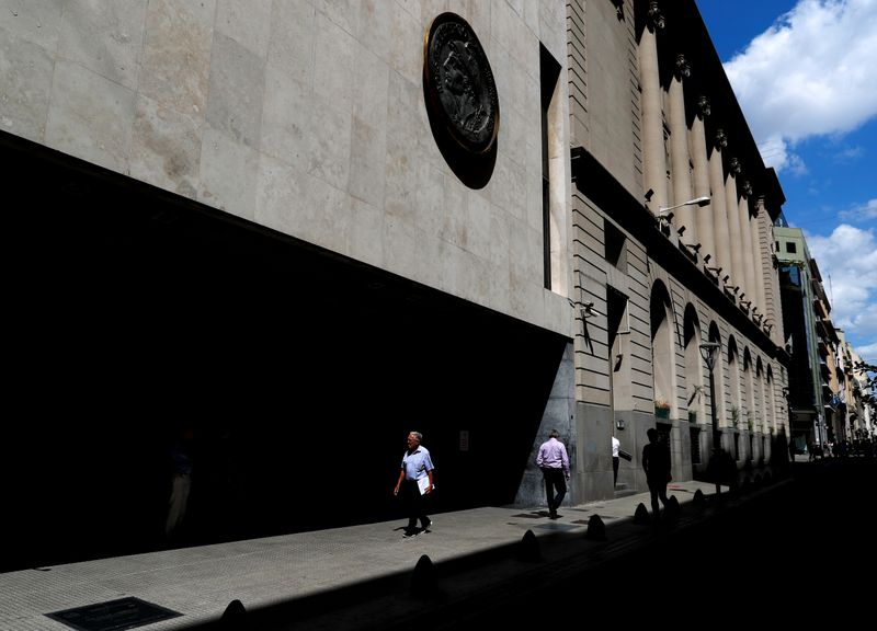 Pedestrians walk past the facade of the Buenos Aires Stock Exchange, in Buenos Aires