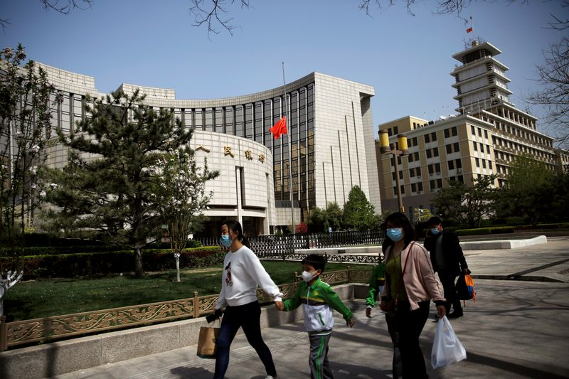 FILE PHOTO: People wearing face masks walk past the headquarters of PBOC, where the Chinese national flag flies at half mast