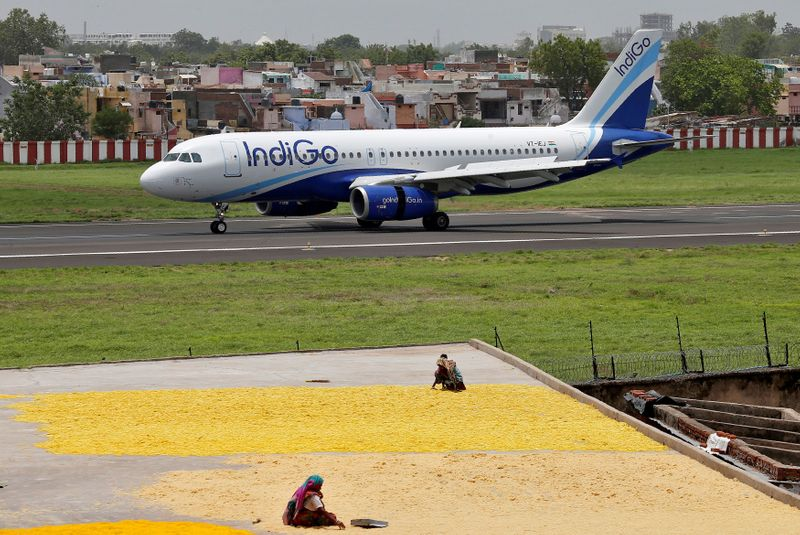 FILE PHOTO: Women spread fryums for drying on a rooftop as an IndiGo Airlines Airbus A320 aircraft moves on the runway after landing at the Sardar Vallabhbhai Patel international airport in Ahmedabad