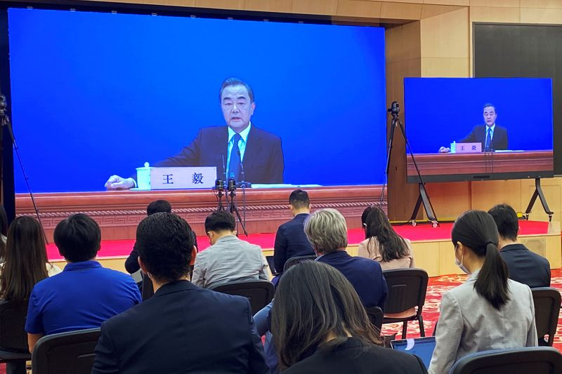 Chinese State Councillor and Foreign Minister Wang Yi is seen on screens during a news conference held via video link in Beijing