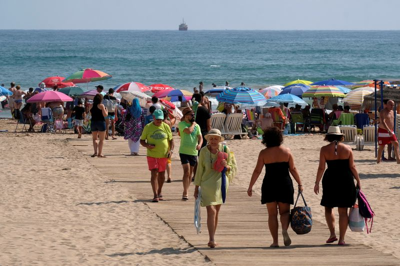FILE PHOTO: Beachgoers gather on the eastern coast to enjoy the last days of the summer season in Gandia near Valencia