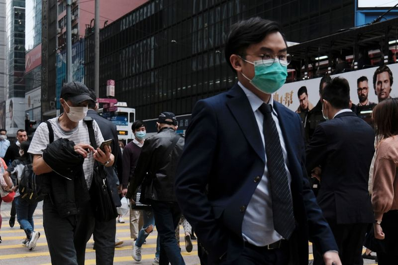 People wear protective face masks as they take their lunch breaks at the financial Central district, following the outbreak of the new coronavirus, in Hong Kong