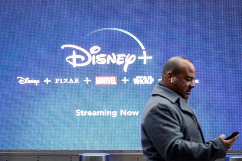 A man looks at his phone as he passes by a screen advertising Walt Disney's streaming service Disney+ in New York