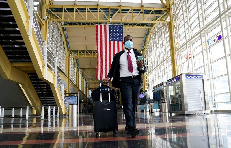 FILE PHOTO: Passenger walks through Reagan National airport as air travel continues to be minimal in Washington