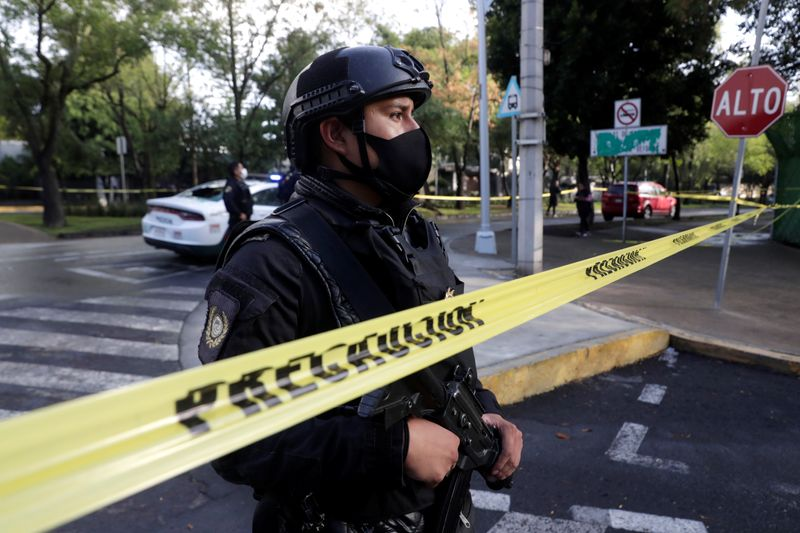 A police officer stands behind a cordon tape at an area where a shooting took place in Mexico City