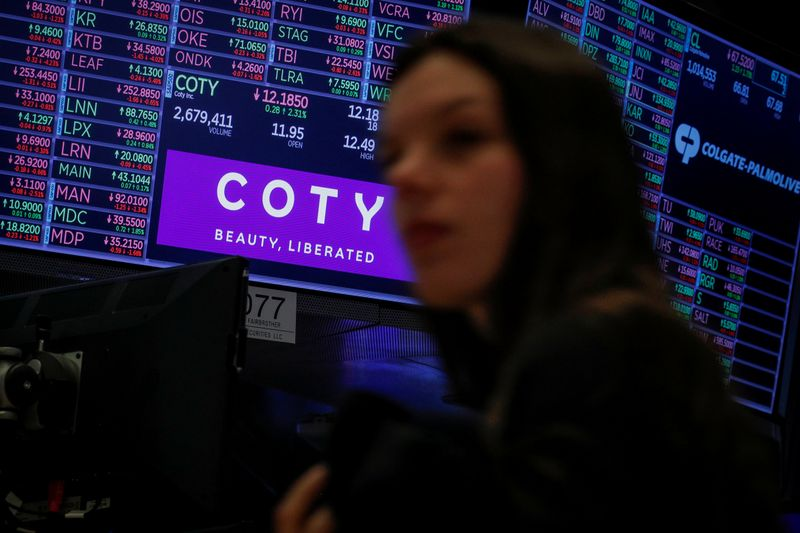 A screen displays the logo and trading information for Coty Inc at the NYSE in New York