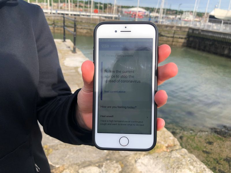 FILE PHOTO:  UK National Health Service employee Anni Adams shows a smartphone displaying the new NHS app to trace contacts with people potentially infected with the coronavirus disease (COVID-19) being trialled on Isle of Wight