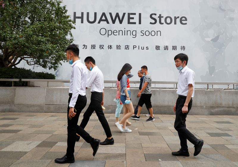 People walk past an advertisement announcing the opening of a HUAWEI store in Beijing