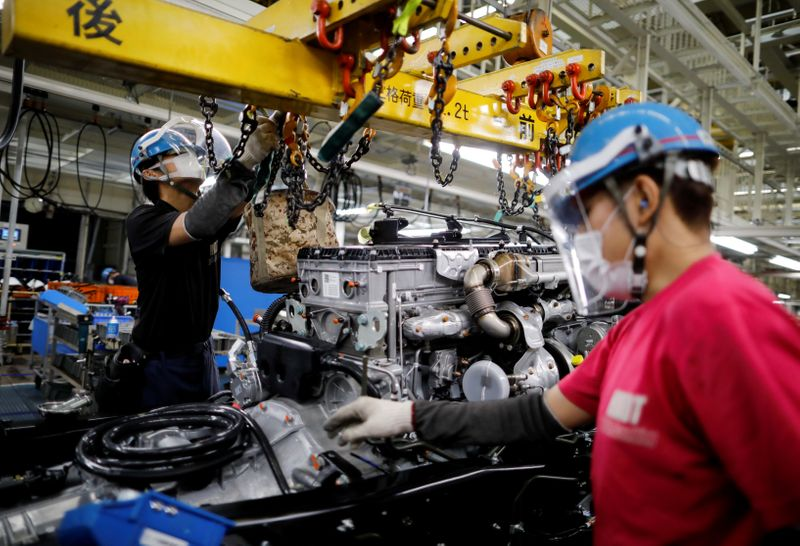 FILE PHOTO: Employees wearing protective face masks and face guards work on the automobile assembly line during the outbreak of the coronavirus disease (COVID-19) at the Kawasaki factory of Mitsubishi Fuso Truck and Bus Corp. in Kawasaki, Japan